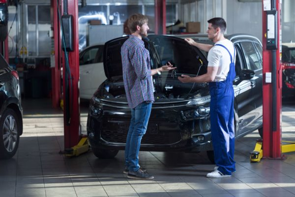 automotive technician talking with male client