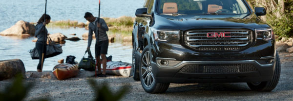 2019 GMC Acadia parked on the water while family unloads kayaks
