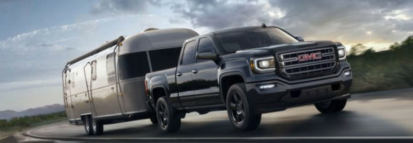 Black 2019 GMC Sierra 1500 hauling a trailer down the highway